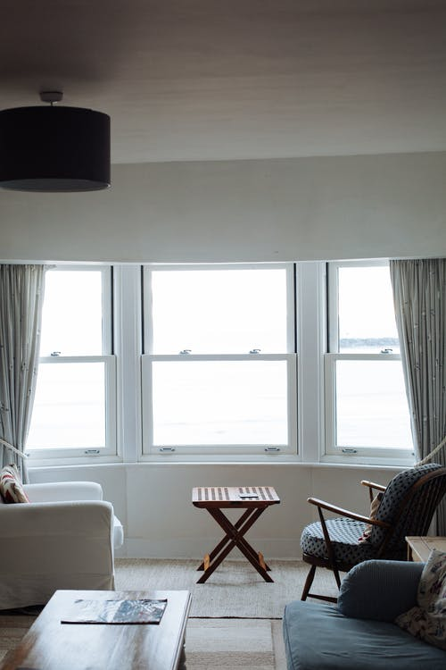 Two Chairs Facing Towards White Casement Window