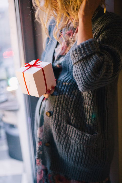 Woman Wearing Blue Knit Cardigan Holding Gift Box Inside Room