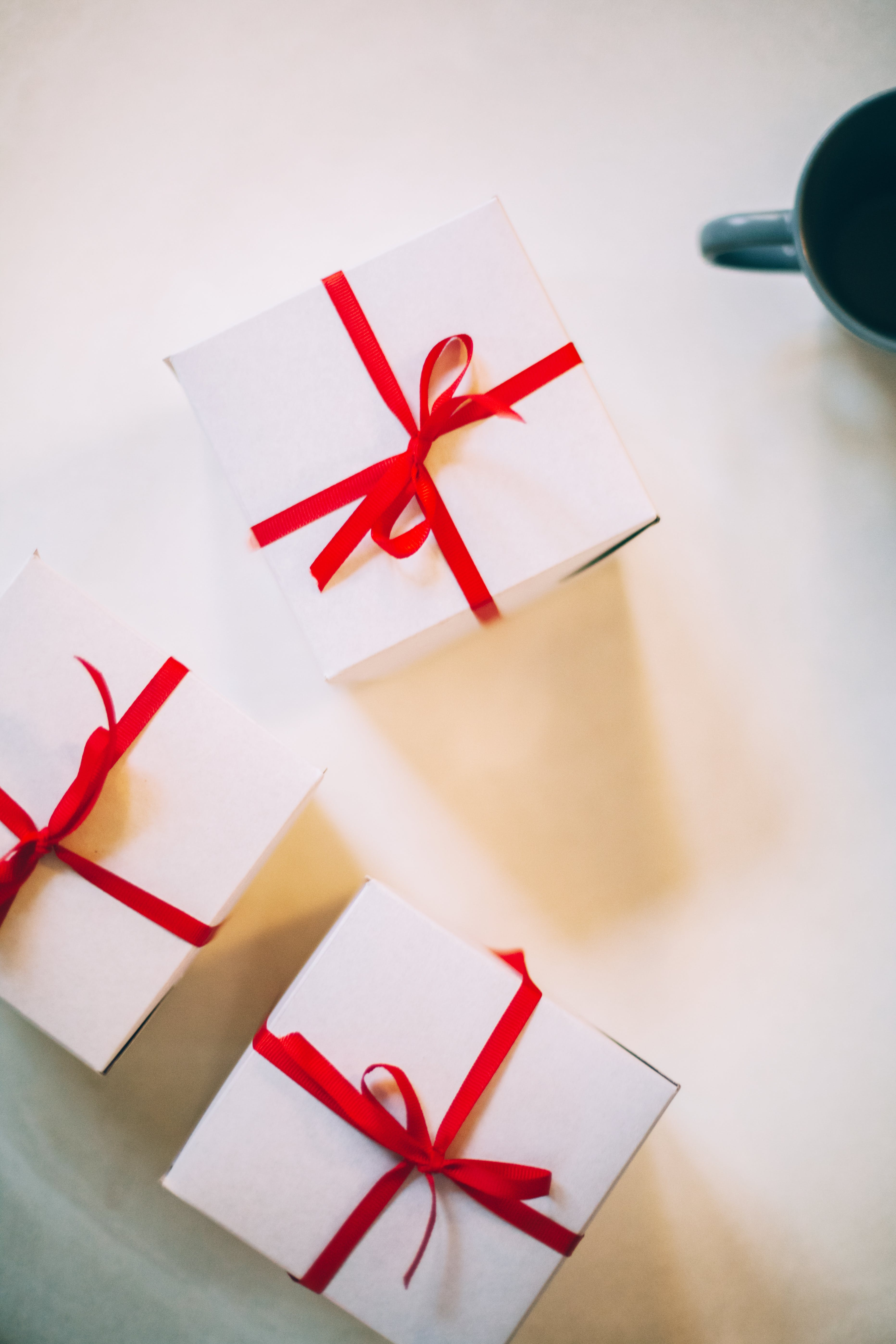 Photography of Three Boxes With Red Ribbons