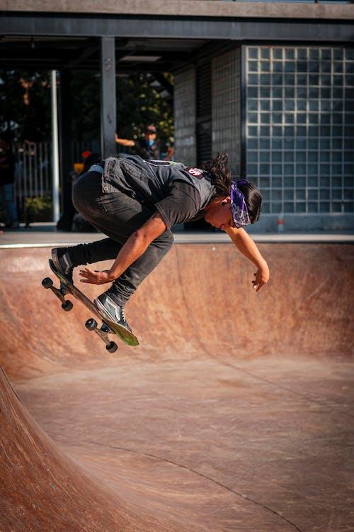 Man in Black T-shirt and Blue Denim Jeans Doing Skateboard Stunts