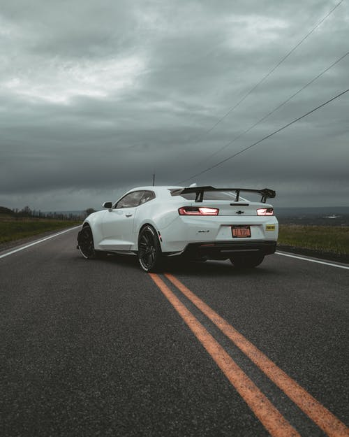 White Porsche 911 on Road Under Cloudy Sky