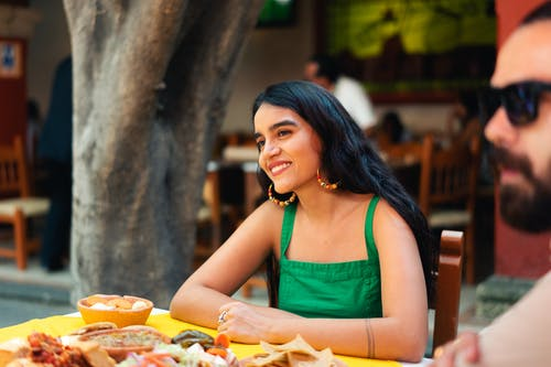 Woman in Green Tank Top Eating Burger