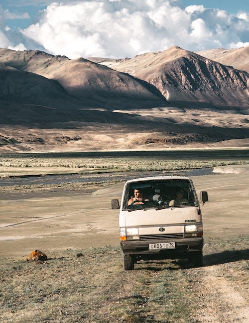 People driving in van in mountainous desert
