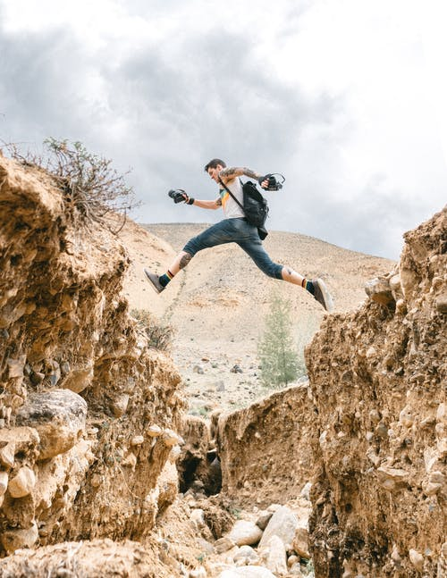 Full body side view of risky male hiker jumping over stony formations during trip in nature with hilly area