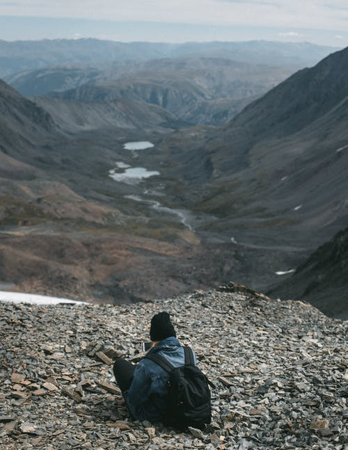 Back view of anonymous hiker with backpack sitting on edge of stony mountain above valley with creek during trip in highlands