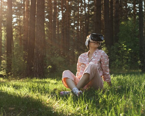 Full body of anonymous female in sleepwear wearing VR headset while exploring virtual reality in sunny woods with tall trees