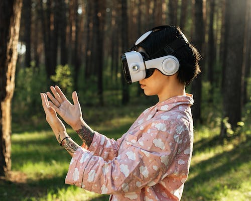 Focused unrecognizable woman in VR headset in woods