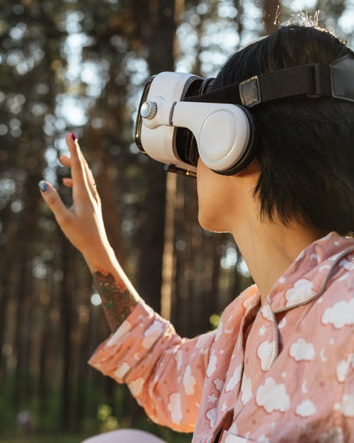 Unrecognizable woman in VR headset near trees