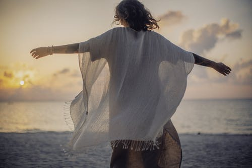Back view of unrecognizable female in light white cape standing with spread arms near sea in evening