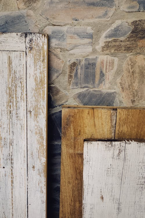 Tops parts of shabby wooden planks with white paint leaning against old multicolored stone wall