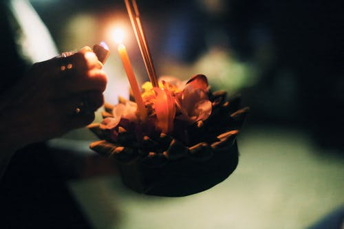 Crop anonymous person burning candle on krathong in hand in darkness on blurred background