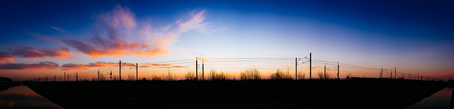 Silhouette of Street Post Light and Grass Under White Cloud and Blue Sky at Daytime