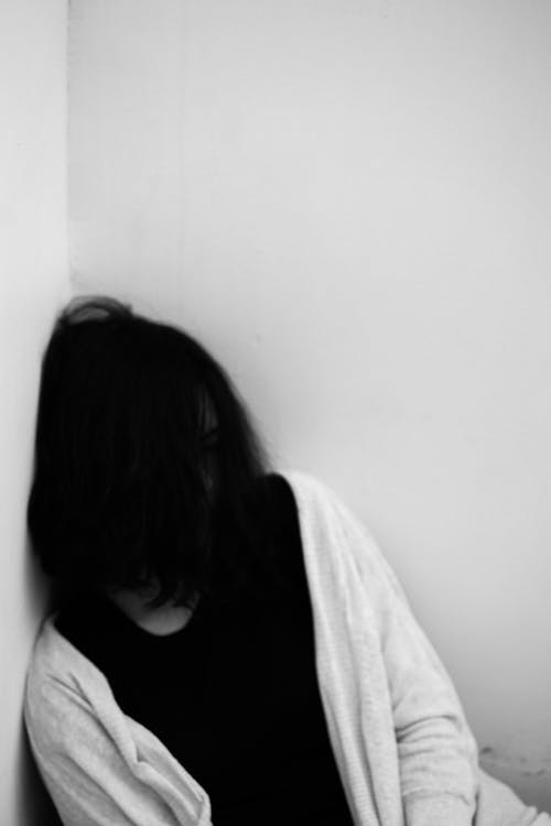 Black and white of female leaning on wall in corner with face hidden by dark hair