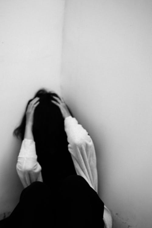 Black and white of female touching head while sitting in room corner with face hidden under hair
