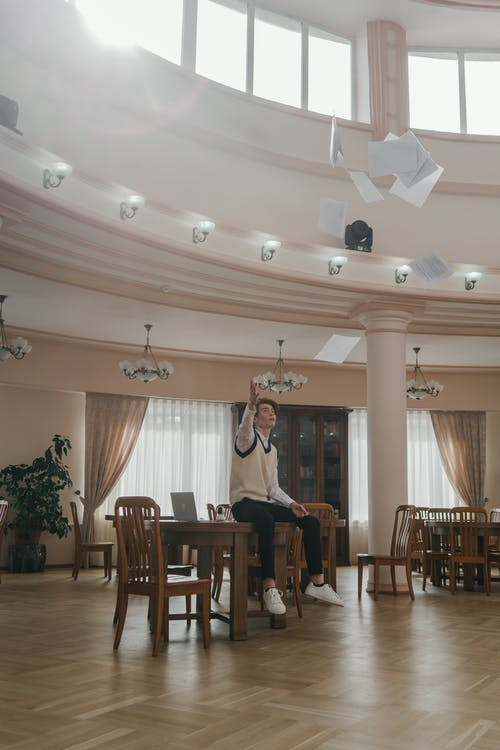 A Man Throwing Papers in the Air while Sitting on a Table