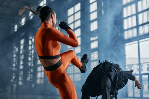 Woman in Orange Sports Bra and Black Shorts