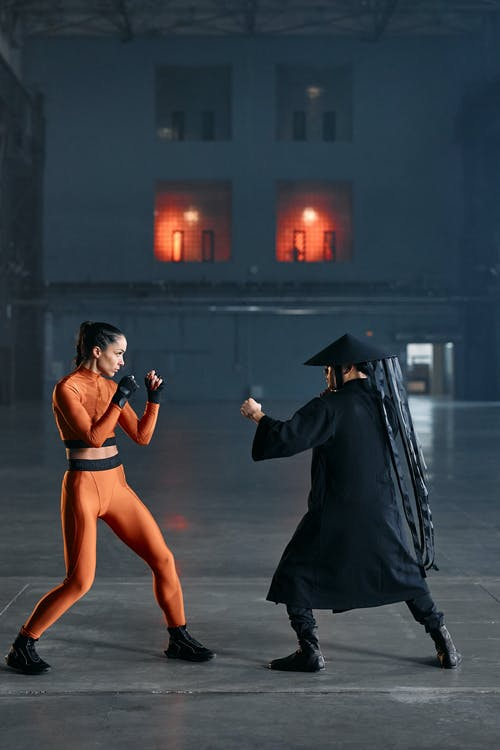 Woman in Black Dress Holding Man in Black Coat
