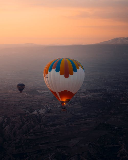 Yellow Red and Blue Hot Air Balloon Floating over the Mountains