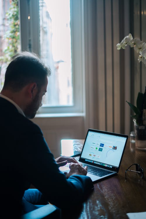 Concentrated businessman typing on laptop while working at table near window in daylight
