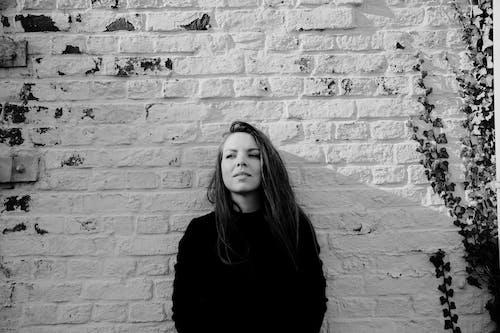 Woman in Black Long Sleeve Shirt Standing Beside Brick Wall