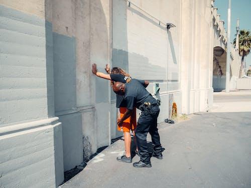 An Officer Frisking a Man