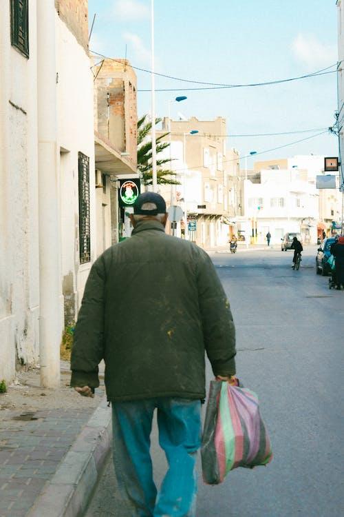 Man in Black Jacket and Blue Denim Jeans Walking on Sidewalk