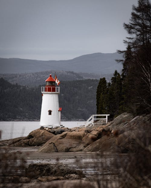 White and Red Lighthouse on Brown Rock Formation Near Body of Water