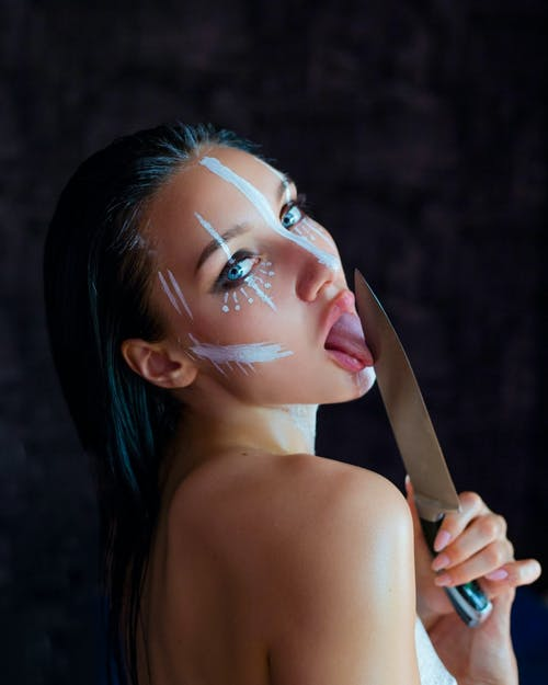 Side view of young female model with long dark wet hair bare shoulders with creative makeup with white stripes painted on face licking knife blade by tongue and mouth opened