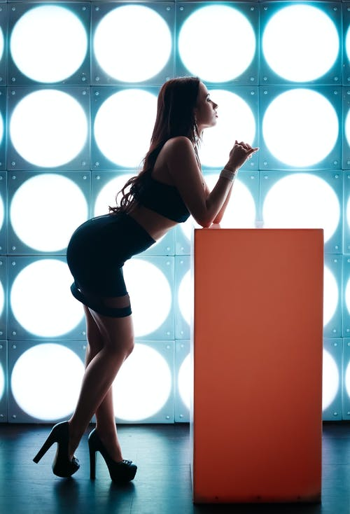 Side view of sensual young female with long hair black brassiere and mini skirt wearing high heeled shoes standing in provocative posture leaning on studio rectangular construction