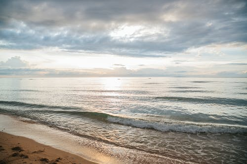 Foamy sea waves rolling on beach against cloudy sunrise sky in morning in nature
