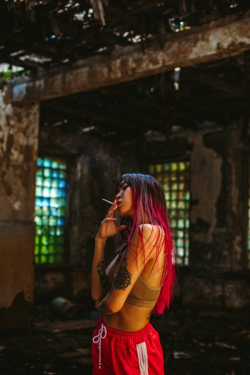 Side view young Asian woman with long pink hair and tattooed arms wearing topic and red sport pants smoking in destroyed building