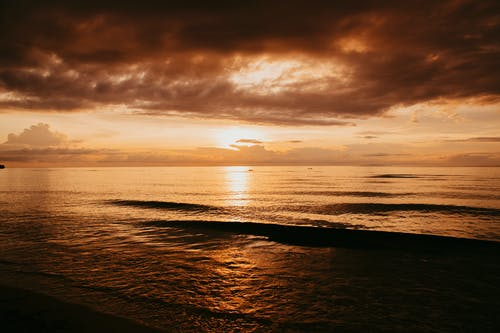 Landscape of ocean shore at sunset with cloudy sky