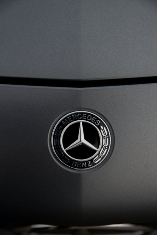 Chrome round shaped logotype of expensive luxury automobile place of dark grey glossy polished car hood