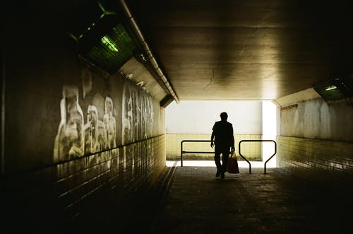 Silhouette of Person Walking on Hallway