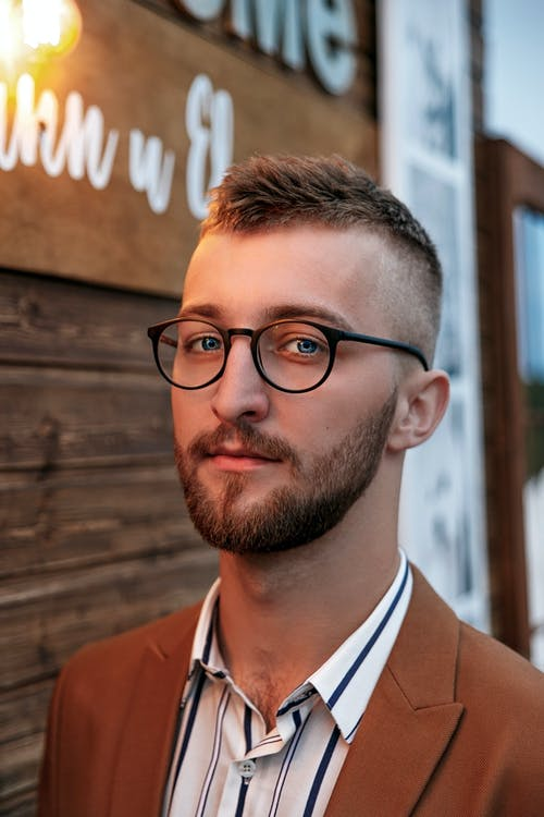 Positive young bearded man in eyeglasses
