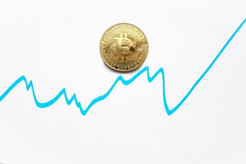 Gold bitcoin cryptocurrency coin and blue graph of changes of value on white background
