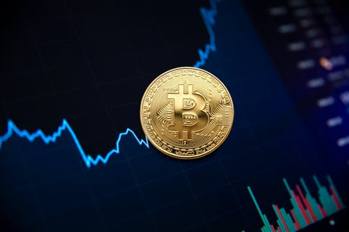 Golden bitcoin coin on background of chart showing indicators of changes in cryptocurrency rates
