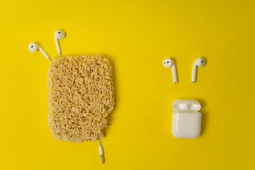 Different earphones placed on yellow background