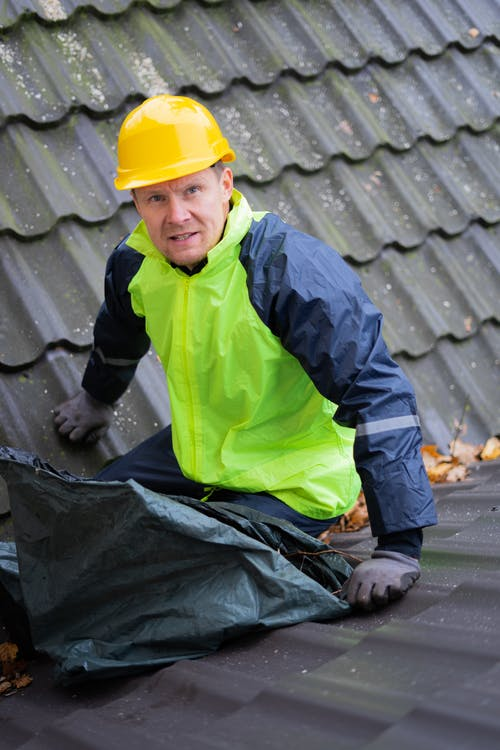 Man in Green and Black Jacket and Yellow Hard Hat Holding a Plastic