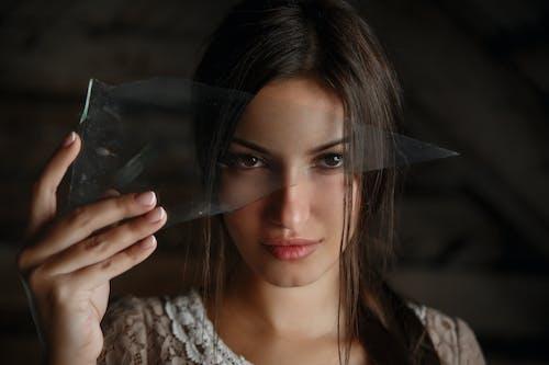 A Woman Holding a Piece of Broken Glass