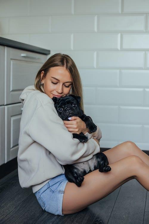 A Woman Petting Her Black Pug