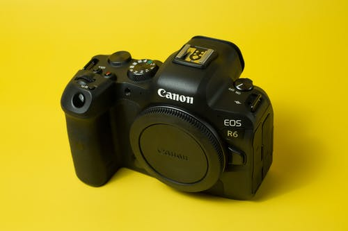 Black Canon Digital Camera on a Yellow Surface