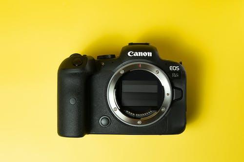 A Black Canon Eos Camera over a Yellow Surface