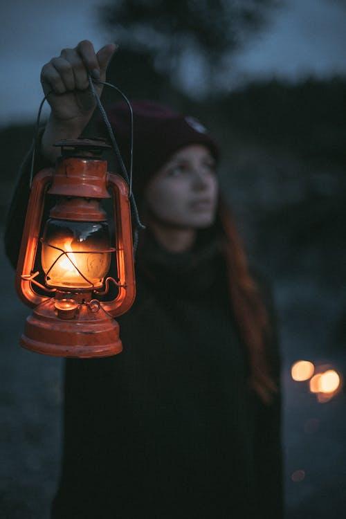 Woman in Black Jacket Holding Orange Lantern