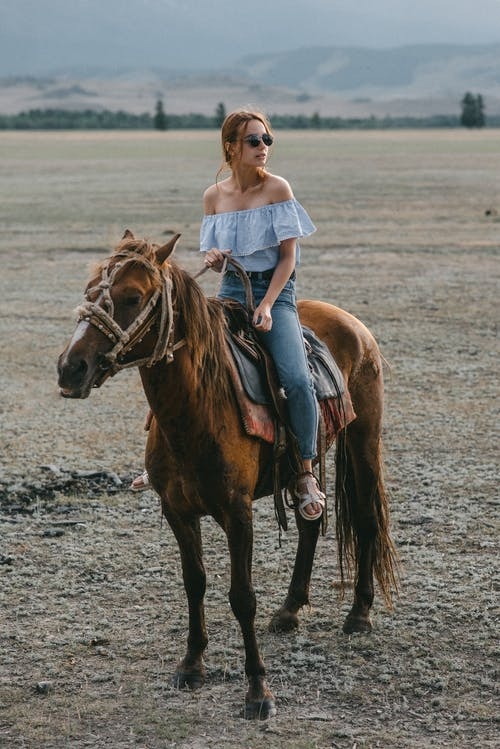Woman in White Dress Riding Brown Horse