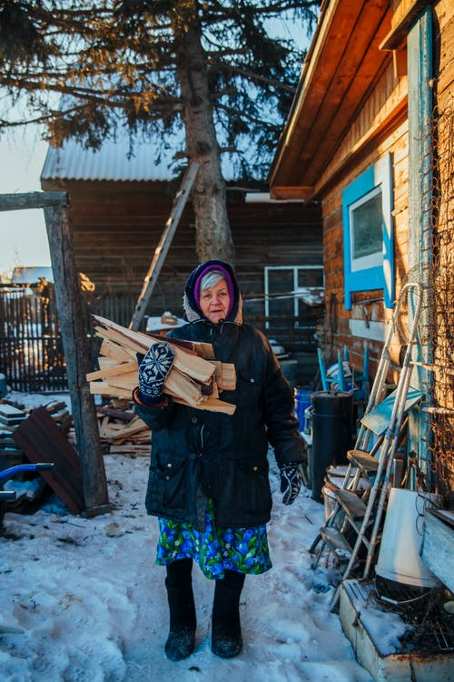 A Woman Carrying a Bunch of Fire Woods