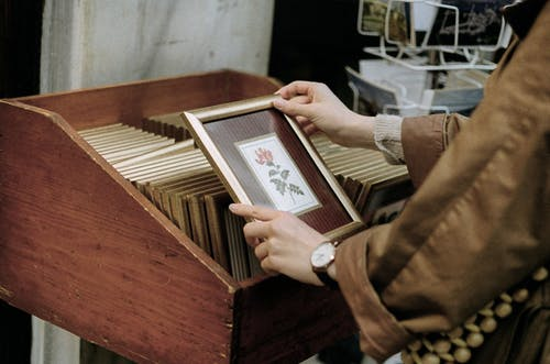 Crop buyer choosing photo frame with flower in shop