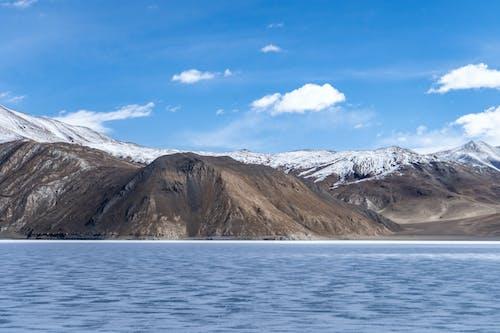 Brown Mountain Near Body of Water Under Blue Sky