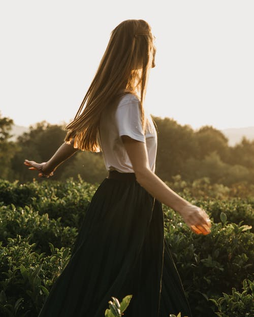 Woman in White Shirt and Black Skirt Standing on Green Grass Field