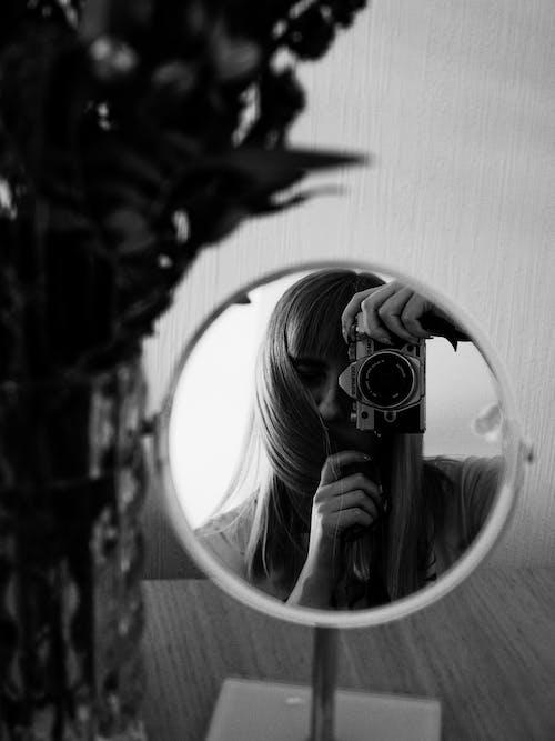 Grayscale Photo of Woman Taking Photo of Bird